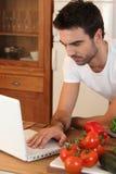 Mann, der Rezept auf dem Internet sucht Lizenzfreies Stockbild