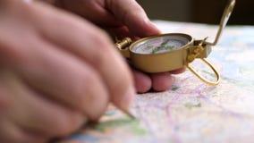 Mann, der Richtung mit einem Kompass auf Hintergrund der Karte sucht stock video