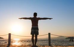 Mann, der in Richtung zum Meer bei Sonnenuntergang steht stockbilder