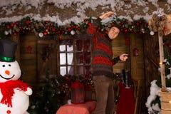Mann, der Rochen vor Blockhaus im Winter hält Stockfoto