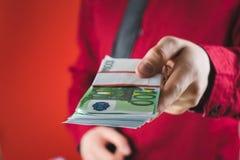 Mann in der roten Klage h?lt heraus ein Pack des Geldes in seiner Hand auf rotem Hintergrund lizenzfreie stockfotografie