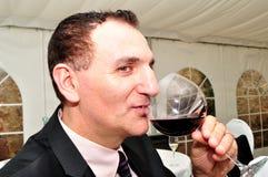 Mann, der Rotwein trinkt Stockbild