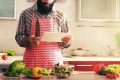 Mann, der Salat macht und Tablette liest Stockfotografie