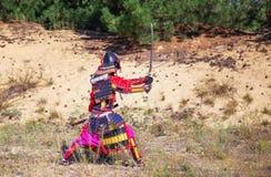 Mann in der Samurairüstung mit Klinge, bereiten vor, um zu kämpfen Stockfotografie