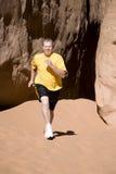 Mann, der in Sand mit gelbem Hemd läuft Lizenzfreies Stockfoto
