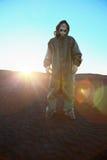 Mann in der schützenden Klage und in den Strahlen der Sonne Stockbild