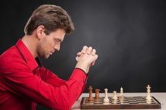Mann, der Schach auf schwarzem Hintergrund spielt Stockfotos