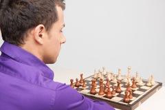 Mann, der Schach auf weißem Hintergrund spielt Lizenzfreie Stockfotografie