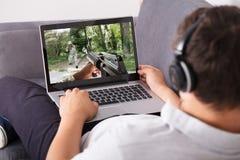 Mann, der schießendes Spiel auf Laptop spielt stockbild