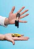 Mann, der Schlüssel und kleines Auto hält Lizenzfreie Stockfotografie