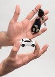 Mann, der Schlüssel und kleines Auto hält Stockfoto