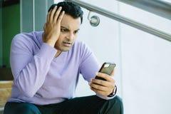 Mann, der schlechte Nachrichten auf Mobiltelefon betrachtet lizenzfreies stockbild
