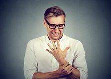 Mann, der schmerzlichen Handgelenkarm hält Verstauchungsschmerz Lizenzfreie Stockfotografie