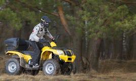 Mann, der schmutziges Viererkabelfahrrad 4x4 ATV reitet Lizenzfreies Stockfoto