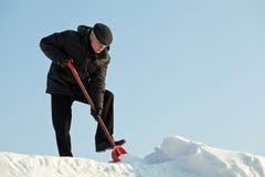 Mann, der Schnee mit einer roten Schaufel schaufelt Stockbild