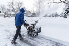 Mann, der Schnee mit einer Schneefräse #1 entfernt Stockbild