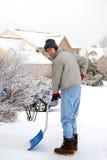 Mann, der Schnee schaufelt Lizenzfreies Stockfoto
