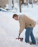 Mann, der Schnee schaufelt Stockfotografie