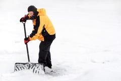 Mann, der Schnee schaufelt Stockfoto