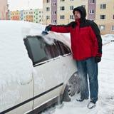 Mann, der Schnee vom Auto löscht Stockbild