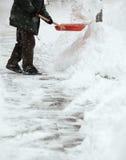Mann, der Schnee vom Bürgersteig schaufelt Lizenzfreie Stockbilder
