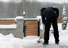 Mann, der Schnee vom Weg schaufelt Stockfoto