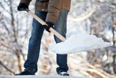 Mann, der Schnee von einer Fahrstraße löscht Lizenzfreies Stockbild