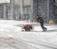 Mann, der Schnee während des Schneesturms schaufelt Lizenzfreie Stockfotografie