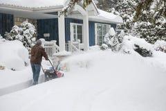 Mann, der Schneekanone im tiefen Schnee verwendet Stockbild