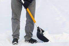 Mann, der Schneeschaufel im Winter verwendet Stockfotos