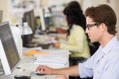 Mann, der am Schreibtisch im besetzten kreativen Büro arbeitet Lizenzfreies Stockfoto