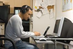 Mann, der am Schreibtisch mit Computern sitzt. Lizenzfreie Stockfotografie