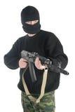 Mann in der schwarzen Maske steht mit Maschinengewehr AK-74 Lizenzfreies Stockbild