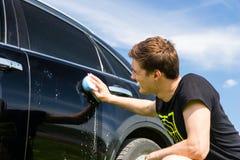 Mann, der schwarzes Auto mit seifigem Schwamm wäscht Lizenzfreies Stockbild