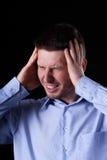 Mann, der schwere Kopfschmerzen hat Stockfotografie