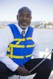 Mann in der Schwimmweste auf Segelboot Stockfotos