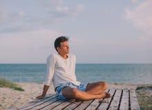 Mann, der am Seestrand sich entspannt Lizenzfreie Stockfotos