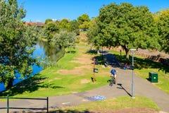 Mann, der sein Fahrrad entlang Torrens-Fluss reitet Lizenzfreie Stockfotografie