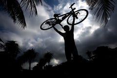 Mann, der sein Fahrrad trägt Stockbild