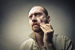 Mann, der sein Gesicht aufräumt Stockfotografie