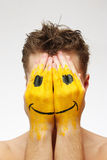 Mann, der sein Gesicht unter Lächelnschablone versteckt Stockfotografie