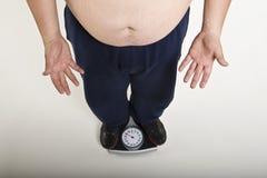 Mann, der sein Gewicht misst lizenzfreie stockfotos