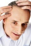 Mann, der sein Haar überprüft Lizenzfreies Stockfoto