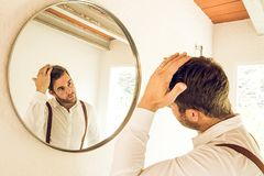 Mann, der sein Haar vor einem Spiegel pflegt lizenzfreies stockfoto