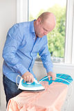 Mann, der sein Hemd bügelt Lizenzfreie Stockfotos
