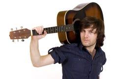 Mann, der seine Akustikgitarre auf Schulter anhält Lizenzfreies Stockfoto