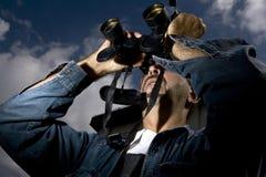 Mann, der seine Binokel verwendet Stockfotos