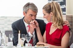 Mann, der seine Frau ` s Hand küsst lizenzfreies stockfoto