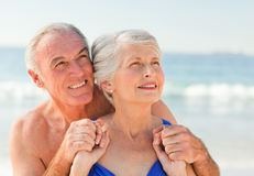 Mann, der seine Frau am Strand umarmt Lizenzfreie Stockfotos