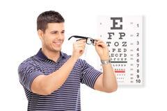 Mann, der seine Gläser vor einer Sehtafel abwischt Stockfoto